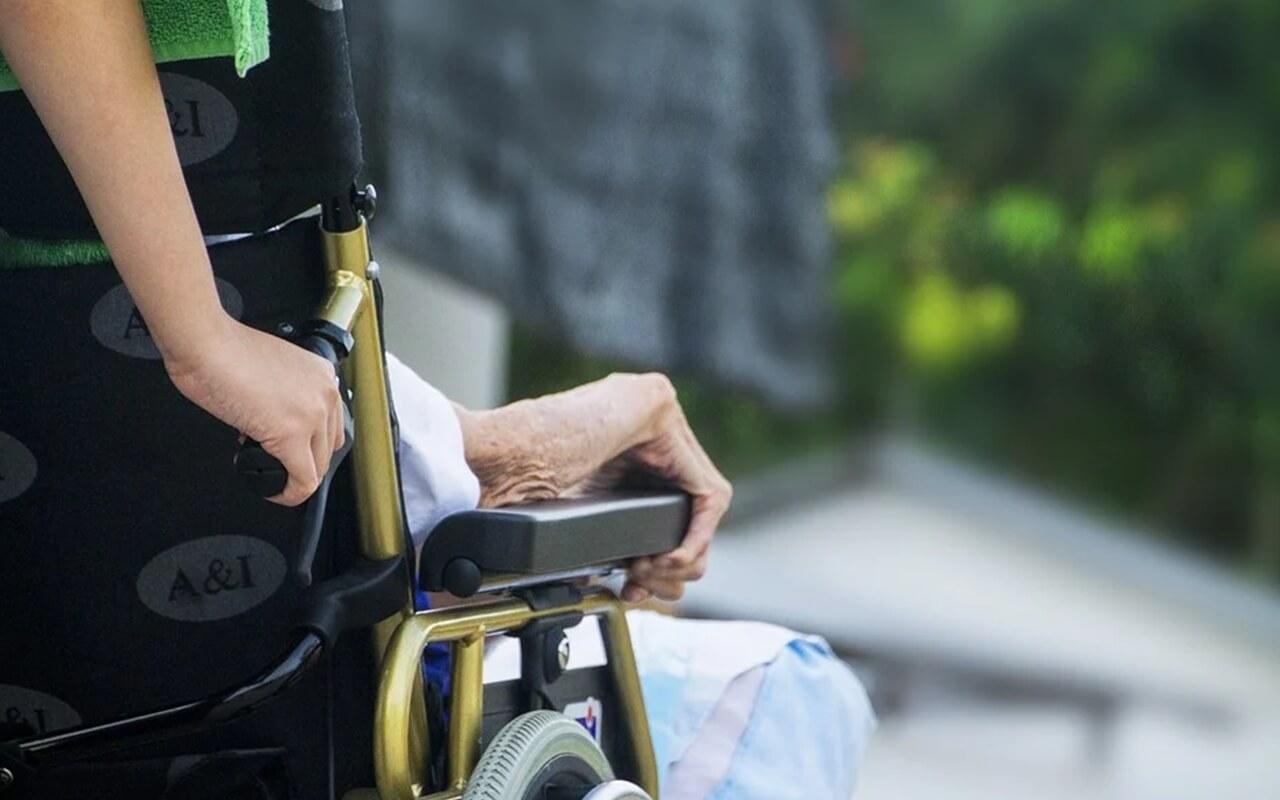 휠체어를 밀어주는 요양사